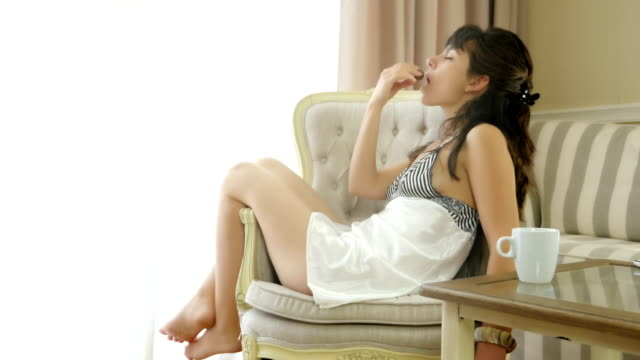 Woman in a nightdress eating chocolate candy with delight video