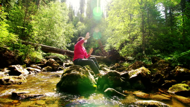 Woman in a pair in VR glasses on the background of a mountain river video