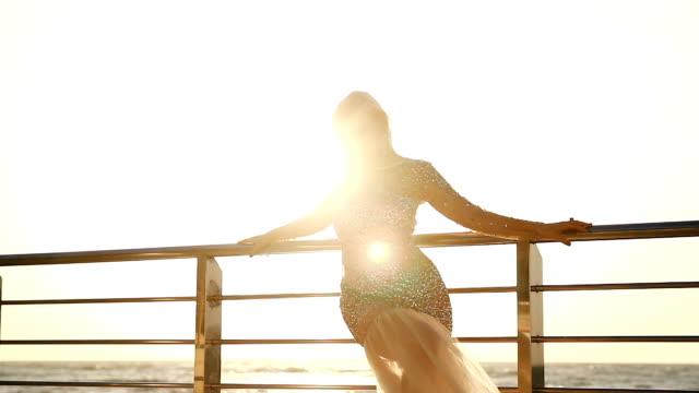 woman in a shiny dress whirls against the sea - giuntura umana video stock e b–roll