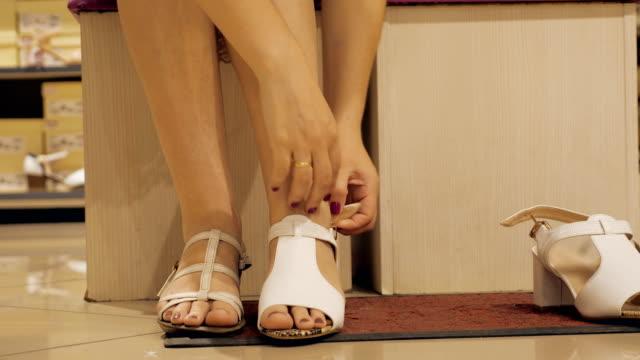 vídeos y material grabado en eventos de stock de mujer en una tienda de zapatos mide sandalias - moda playera