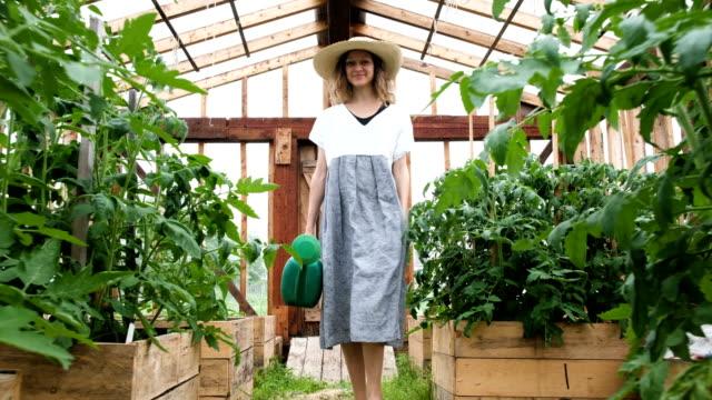 sera sulama olabilir ile kadın bir hasır şapka ve kıyafet gider - bahçe ekipmanları stok videoları ve detay görüntü çekimi