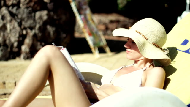 stockvideo's en b-roll-footage met woman in a sunhat reading by pool - newspaper beach