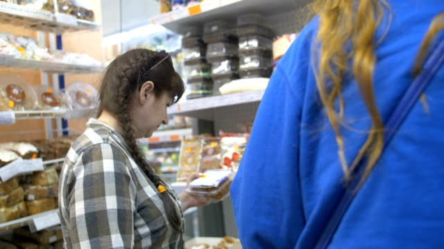 woman in a supermarket chooses sweets, cakes video