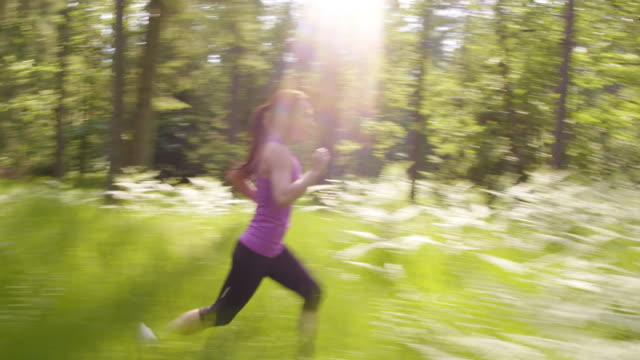TS Woman in a violet top running through the forest video