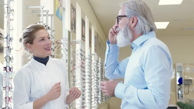 Woman in a white coat working in optics shop helping a senior man with beard pick his new glasses video