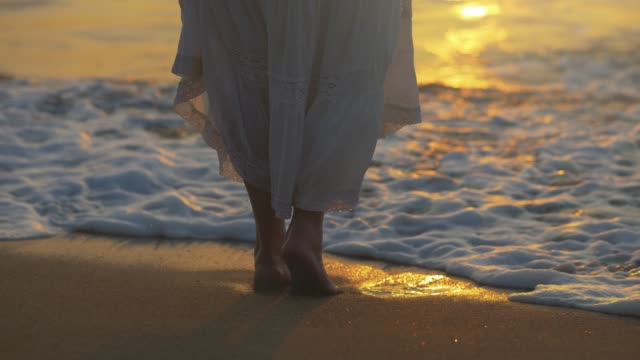 vídeos de stock e filmes b-roll de a woman in a white skirt bounces off sea wave. sunset light. slow motion shot. 4k, uhd - saia