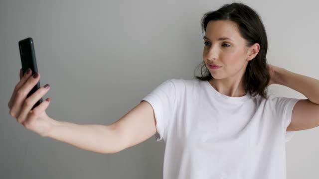 woman in a white t-shirt on a light wall makes a selfie - maglietta bianca video stock e b–roll