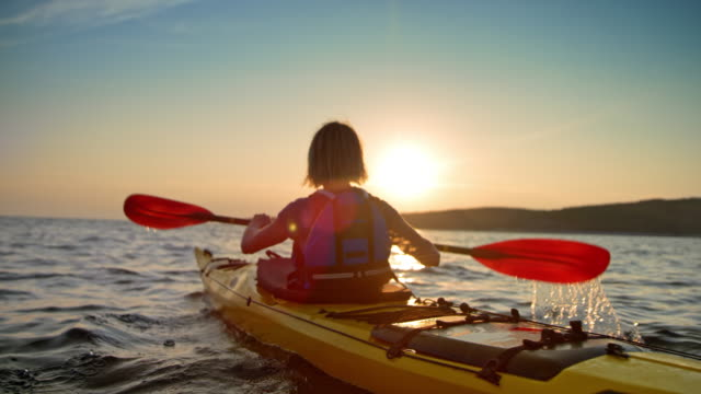 vídeos de stock, filmes e b-roll de slo mo mulher em um caiaque de mar amarelo, passando sobre a água, ao pôr do sol - remo esporte aquático