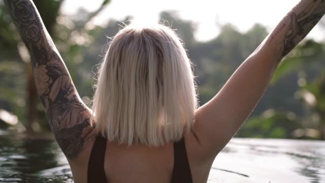 Kvinna i en infinity pool med armarna upp video