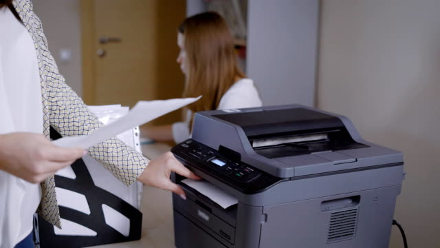 woman in an office is taking papers from printer, working day in sales department of a small business company woman in an office is taking papers from printer, working day in sales department of a small business company, traditional document management printmaking technique stock videos & royalty-free footage