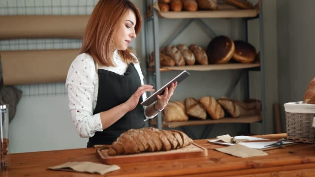 Woman in bakery using tablet video