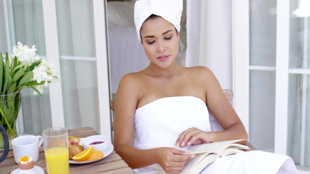 Woman in bath towel reading book at table Cheerful young adult woman wrapped in white bath towel reading book at table with flowers  coffee  juice and fruit wearing a towel stock videos & royalty-free footage