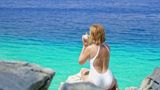 Woman in bathing suit holding seashell up to ear at sunny summer blue ocean Woman in bathing suit holding seashell up to ear at sunny summer blue ocean. MS,real time. Shoot in 8K resolution. animal shell stock videos & royalty-free footage