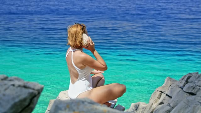 Woman in bathing suit meditating,holding seashell up to ear at sunny summer blue ocean