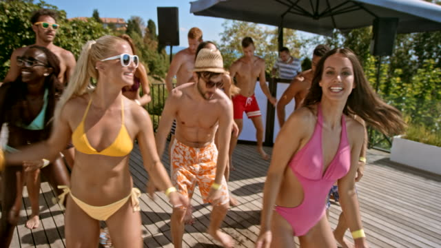 Woman  in bathing suit posing for the camera while dancing a group dance with her friends at a pool party video