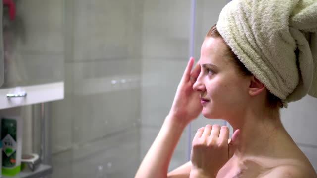 女性の顔のクリームを適用するバスローブ - スキンケア点の映像素材/bロール