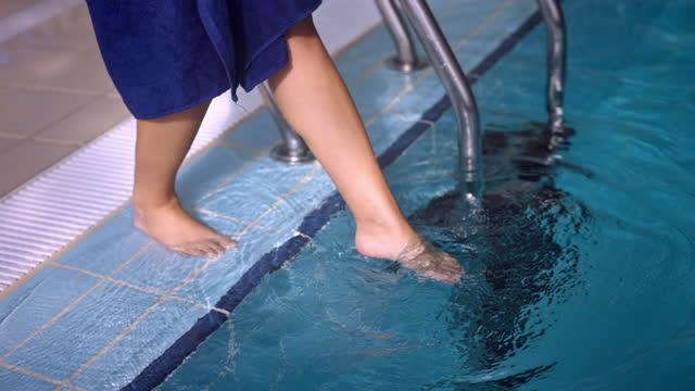 donna in accappatoio che tuffo piede nella piscina coperta - dito del piede video stock e b–roll