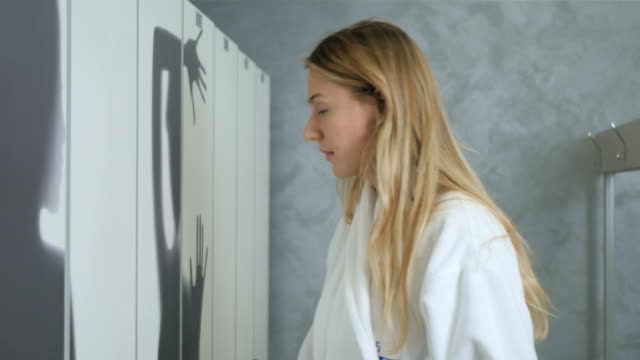 Woman in bathrobe takes the phone from cupboard in dressing room Young blonde in bathrobe comes to dressing room in spa center. Pretty woman open her cupboard and take a phone in hands from the shelf. The woman uses the smartphone and put it back on the shelf in the cupboard. locker stock videos & royalty-free footage
