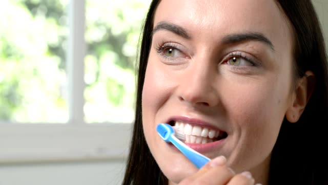 Woman In Bathroom Brushing Teeth With Manual Toothbrush video