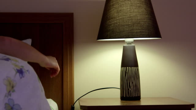 Woman in bed falling asleep turning off bedside lamp at night video