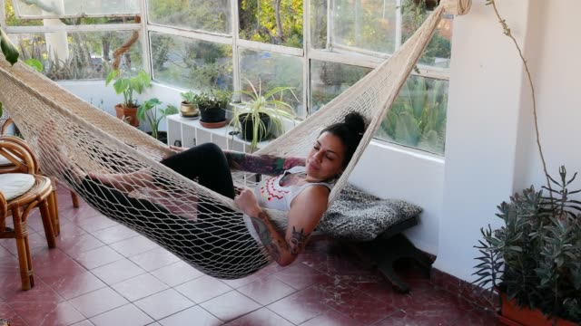 woman in bed relaxing - tattooed mexican at home day dreaming in bed - gente serena video stock e b–roll