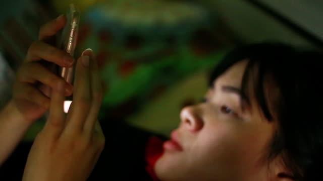 スマート フォンと一緒にベッドで hd: 女性 - スマートフォン点の映像素材/bロール