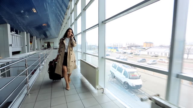 Woman in beige coat talks on phone and goes through airport
