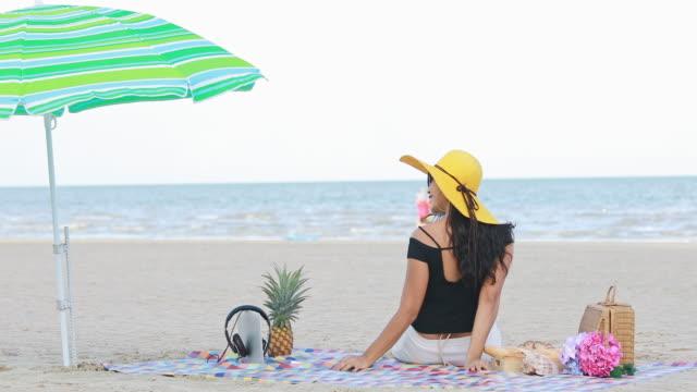 woman in bikini and summer hat lying on tropical beach - opalenizna filmów i materiałów b-roll
