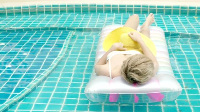vídeos de stock, filmes e b-roll de mulher no biquini no colchão inflável na piscina - inflável