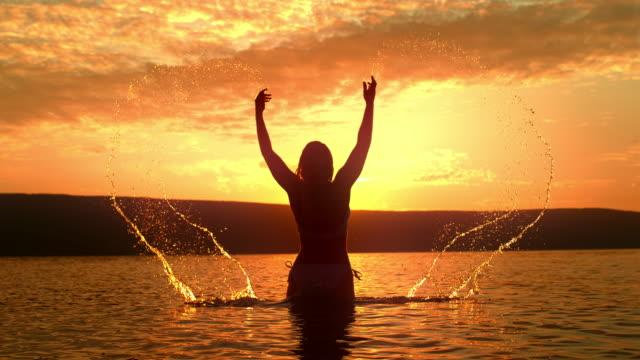 stockvideo's en b-roll-footage met super slo mo vrouw in bikini spattend water over zich - er even tussenuit
