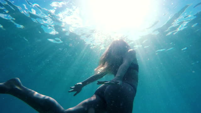 Woman in Bikini swimming underwater towards surface like a mermaid with beautiful sun flares in slow motion. video