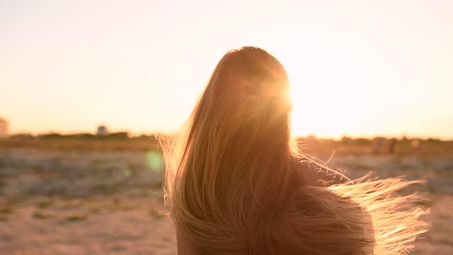 kvinna i bikini baddräkt rufsar hennes långa hår mot att sätta solen på stranden - brunbränd bildbanksvideor och videomaterial från bakom kulisserna