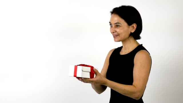 Woman in black dress gets a present in a white gift box with red ribbon