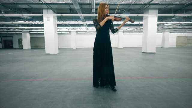 Woman in black dress plays violin, holding it in hands. Woman in black dress plays violin, holding it in hands. 4K classical concert stock videos & royalty-free footage