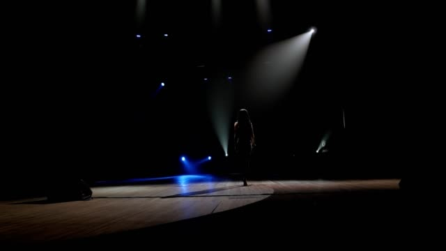 A woman in black suits goes on stage to a microphone in the dark.