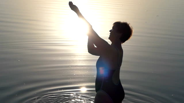 A woman in black swimming suit stands in lake water video