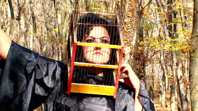 Woman In Black With Cage On Her Head In Autumn Forest video