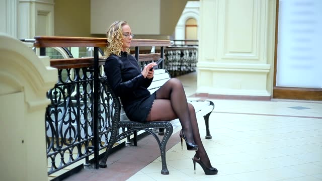 kvinnan i svart med telefon på bänk - strumpbyxor bildbanksvideor och videomaterial från bakom kulisserna
