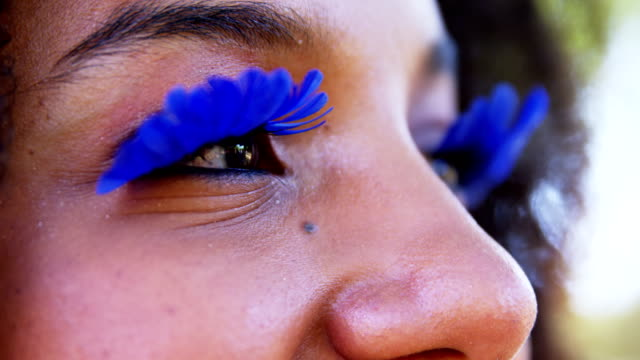 Woman in blue eye lashes at music festival 4k video