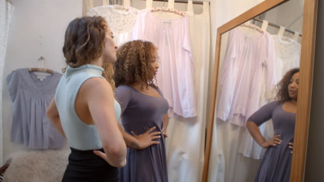 Woman in boutique changing room with friend trying on dress Woman in boutique changing room with friend trying on dress dress stock videos & royalty-free footage