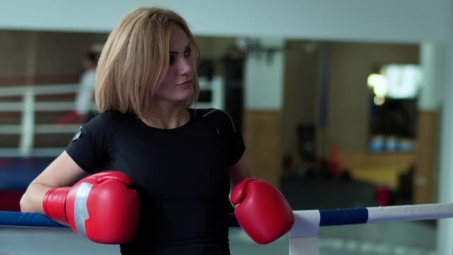 Woman in boxing gloves leans at ropes of boxing ring video