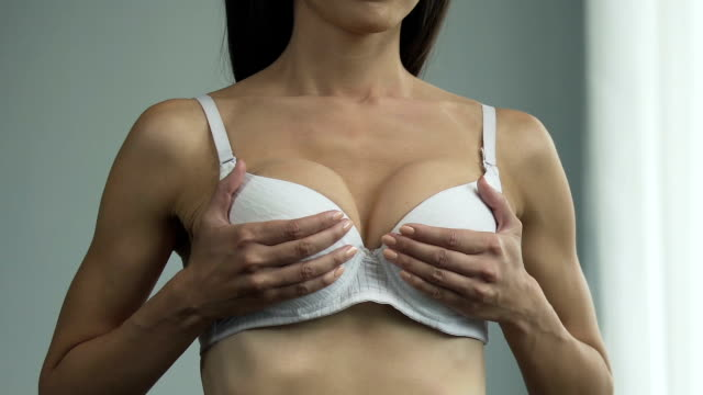 vídeos de stock e filmes b-roll de woman in bra looking in mirror, lifting breasts up, sighing heavily, unhappy - teta