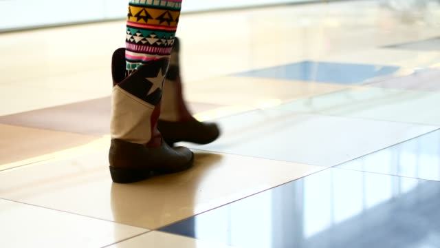 woman in brown boots in a shopping center