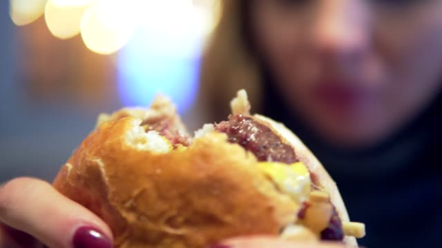 woman in cafe eating hamburger - mordere video stock e b–roll