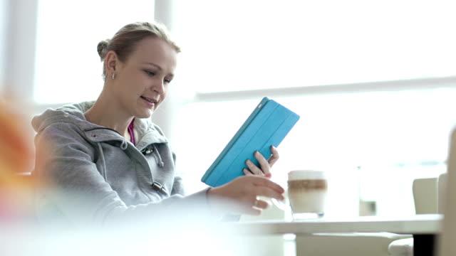 женщина в кафе с помощью ее сенсорная панель - кофе брейк стоковые видео и кадры b-roll