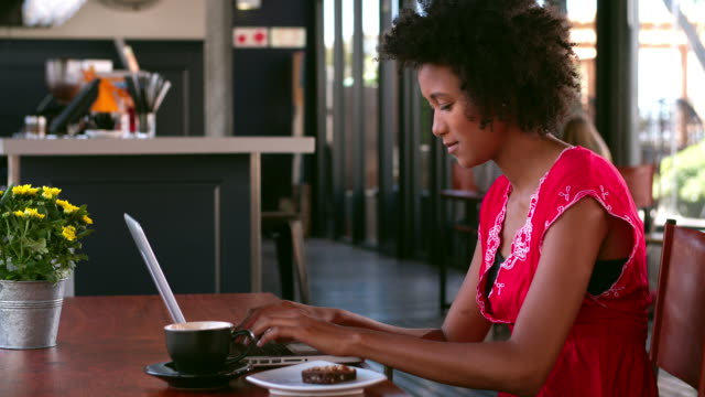 Woman In Cafe Working On Laptop And Answering Phone video