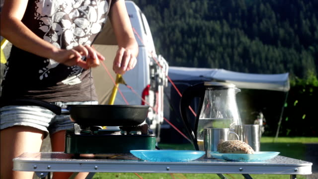 Woman in camping frying eggs and makes coffee for breakfast video
