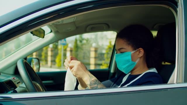 vídeos de stock, filmes e b-roll de mulher no carro colocando máscara e luvas durante epidemia - consciência negra