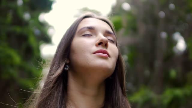 woman in closed eyes low angle shot, beautiful brunette feels nature oneness - медитировать стоковые видео и кадры b-roll