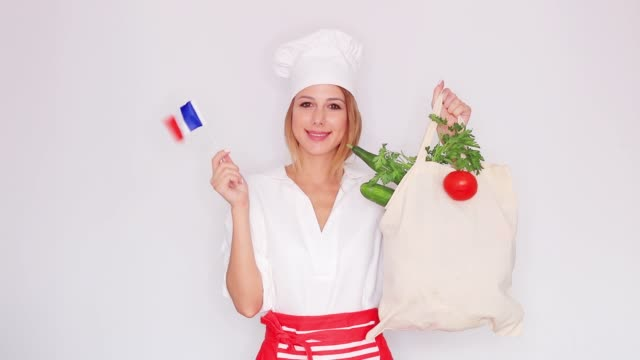 woman in cook uniform holding bag and french flag video